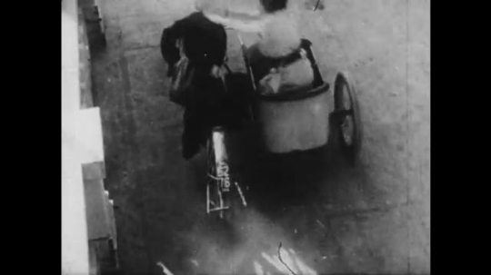 1910s: man with mustache smashes motorcycle through railing and plunges off bridge. Man in cowboy hat throws rope and lassoes woman in midair. man falls in water.