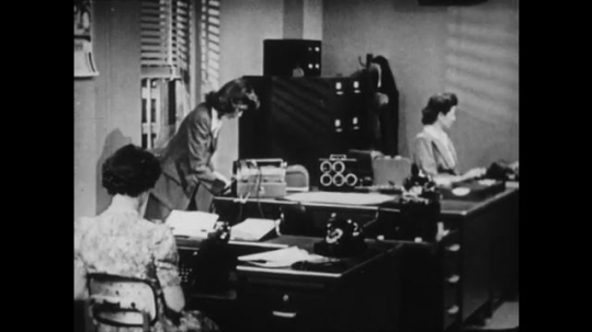 1940s: UNITED STATES: ladies work in office. Typewriter on table. Broken typewriter.