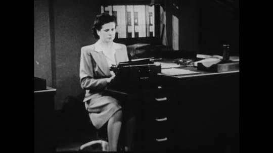 1940s: UNITED STATES: lady types on typewriter at desk. Man repairs machine at bench