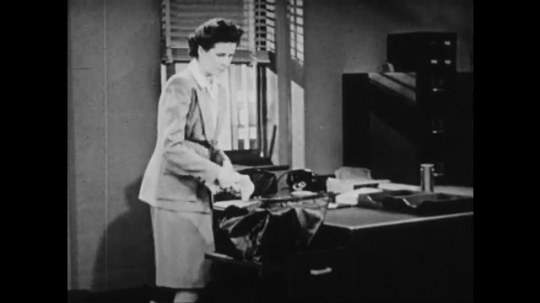 1940s: UNITED STATES: lady wipes down typewriter and cover. Lady dusts machine