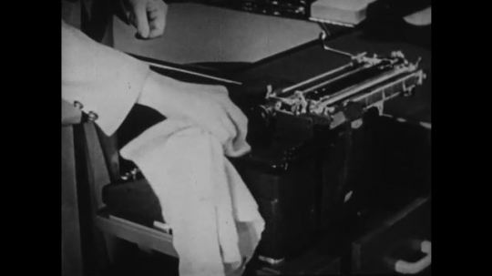 1940s: UNITED STATES: hands clean typewriter workings.