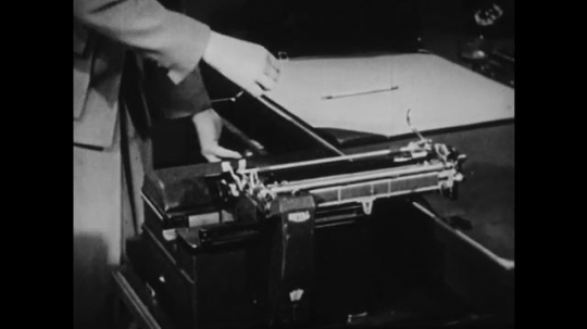 1940s: UNITED STATES: hands open drawer. Hands dust down typewriter workings. Inside wires and keys on typewriter. Pencil points at typewriter workings