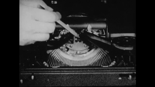 1940s: UNITED STATES: hand points pencil at typewriter workings. Hand dusts internal mechanism of typewriter with brush