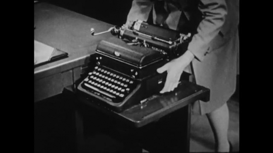 1940s: UNITED STATES: lady lifts typewriter onto table. Lady cleans under typewriter.