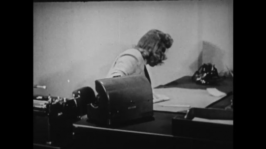 1940s: UNITED STATES: lady pours fluid on to cloth. Lady cleans typewriter