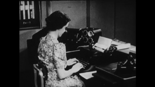 1940s: UNITED STATES: side profile as lady types on typewriter. Front view of secretary typing