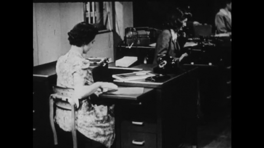 1940s: UNITED STATES: lady closes papers on desk. Lady knocks machine on floor. Lady puts on jacket at desk. Lady types.