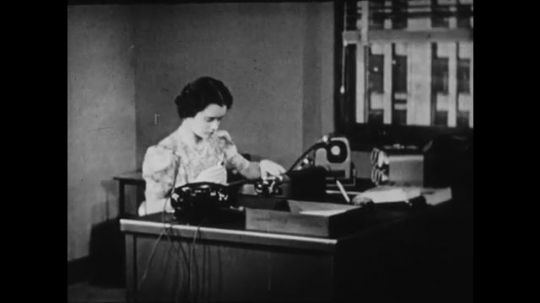 1940s: UNITED STATES: lady works at desk. Lady inspects internal workings of typewriter. Man looks inside typewriter