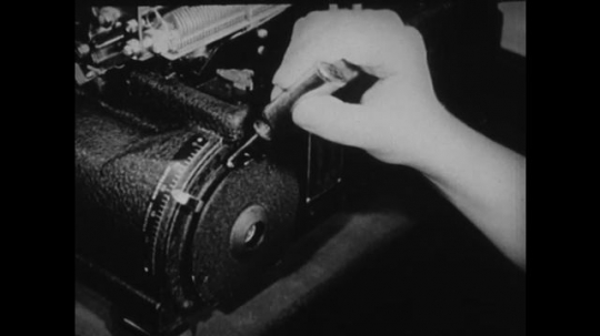 1940s: UNITED STATES: hand holds screwdriver by typewriter.