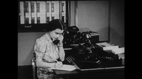 1940s: UNITED STATES: lady in office speaks on telephone. Lady keys in information.