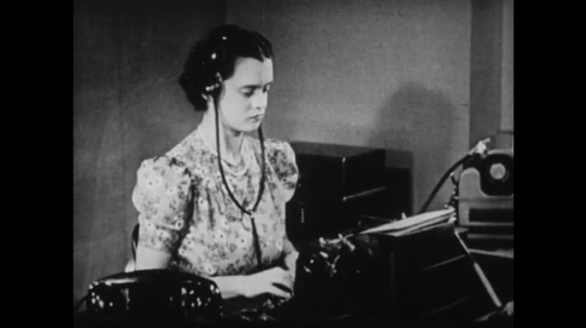 1940s: UNITED STATES: lady types on typewriter in office. Lady takes paper from typewriter