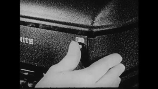 1940s: UNITED STATES: fingers flick switch on machine. Close up of ribbon on typing machine. Lady typing