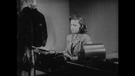 1940s: UNITED STATES: girl types on typewriter at desk