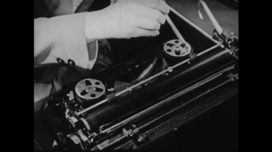 1940s: UNITED STATES: hands wind on typewriter ribbon. Inside of typewriter