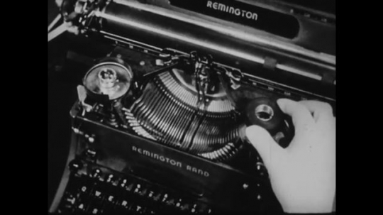 1940s: UNITED STATES: hands place new ribbon ink inside typewriter. Pencil points at typewriter components