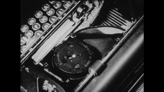 1940s: UNITED STATES: hand removes capsule inside typewriter. Pencil points at typewriter