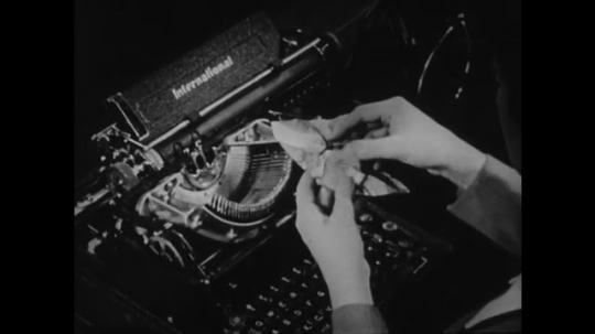 1940s: UNITED STATES: hand unwraps new printer ink ribbon from paper. Fingers install new ink in typewriter