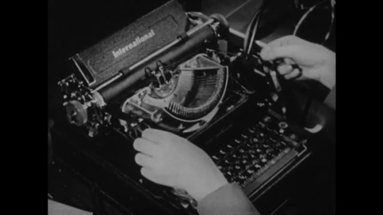 1940s: UNITED STATES: hands install new printing ink ribbon in typewriter.