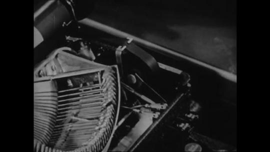 1940s: UNITED STATES: typewriter keys move as keys pressed. Pencil points at teeth on wheel.