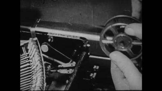 1940s: UNITED STATES: fingers wind up slack on printing ribbon ink.