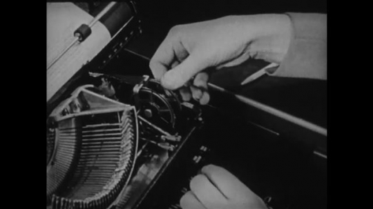 1940s: UNITED STATES: fingers turn spool inside typewriter. End of ribbon roll.