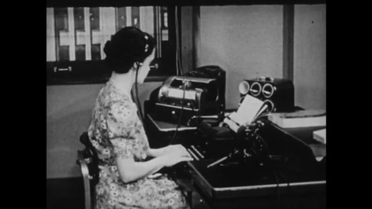1940s: UNITED STATES: side profile of lady typing. Finger pushes latch on cover. Secretary works at desk.