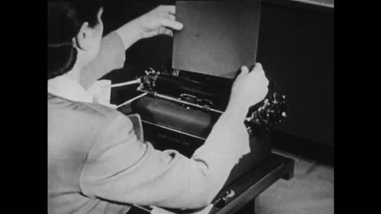 1940s: UNITED STATES: lady puts paper in typewriter. Lady rolls cardboard through typewriter