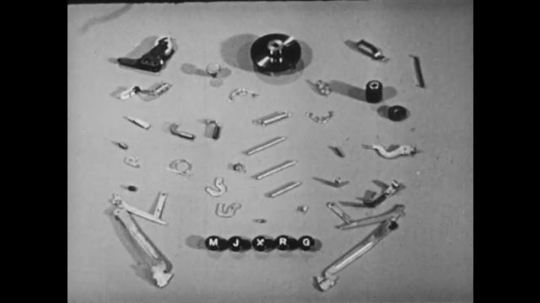 1940s: UNITED STATES: pieces of typewriter on table. Internal workings of typewriter