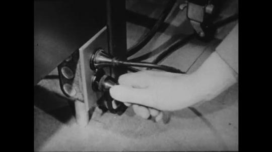 1940s: UNITED STATES: loose plug on typewriter. Hand pushes in plug. Lady tries to fix typewriter at desk.