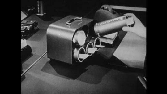 1940s: UNITED STATES: hand puts capsules inside machine for testing. Paper in holes