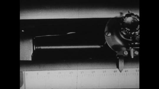1940s: UNITED STATES: typewriter component. Lady looks at broken typewriter