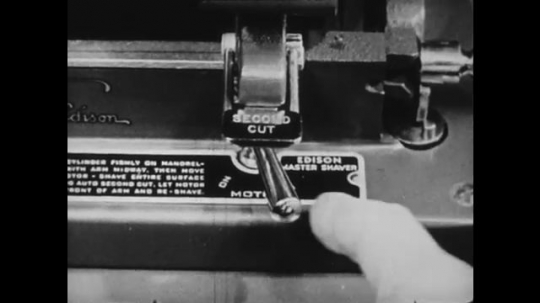 1940s: UNITED STATES: master shaver machine, Hand moves latch on machine