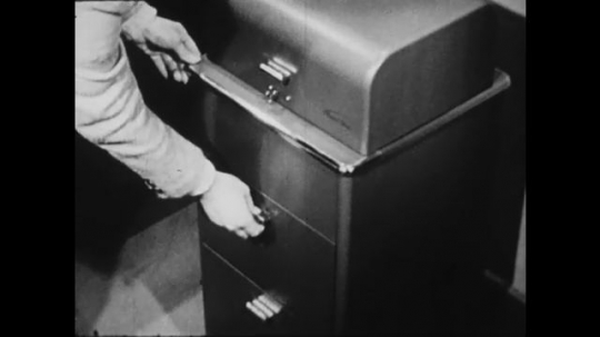 1940s: UNITED STATES: hand opens desk drawer. Hand removes ink. Hand cleans down machine with cloth