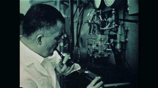 1970s: Man with equipment. Lab equipment. Man next to tank. Man looks in tank window. Man with equipment. Man writing. Man talking at desk. Underwater view of logo.