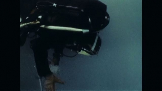 1970s: Underwater footage of diver. Close up of man talking.