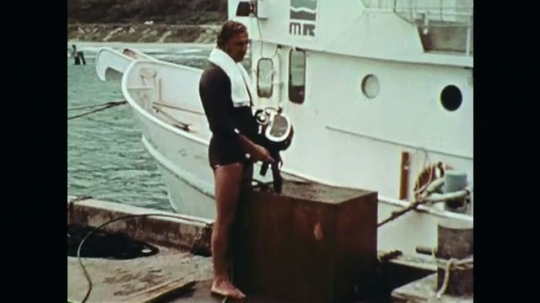 1970s: Man rinses off mask on pier, zoom in, man talks.
