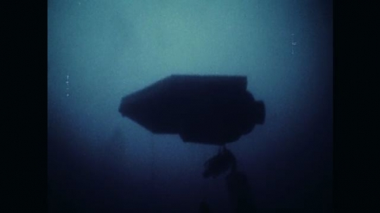 1970s: Underwater view, underside of diving station. Men on diving station. View of tanks.