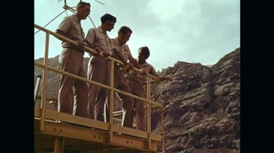 1970s: Men on diving station, zoom in on man talking. Handheld tracking shot around diving station. View down ladder.