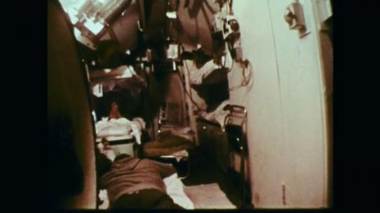 1970s: Bunks in diving station. Man talking next to bunks. View of equipment. Man talking. Equipment. Man talking. Men inside station with diver.