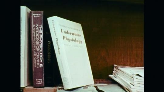 1970s: Books on shelf. Close up, man talking.