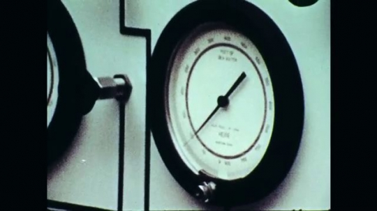 1970s: Close up of gauge. Man talking next to control panel.