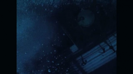 1970s: Underwater view of air bubbles, diving station submerging. View of diving station, tilt up to ocean surface.
