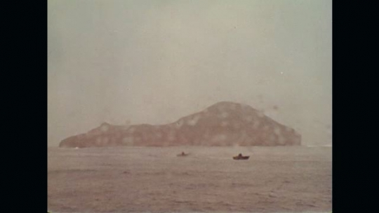 1970s: Long shot, boats near island. Waves crash on coastline. Zoom in on weather vane. Hands open map.