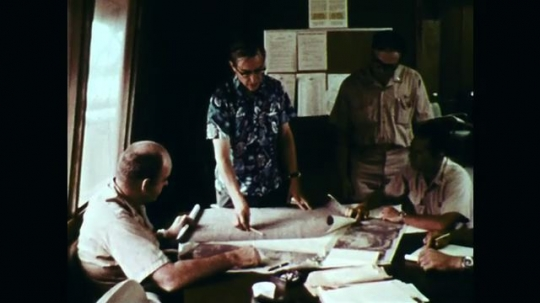 1970s: Men look at plans around table, zoom in on man talking. Map on table, man points to map.