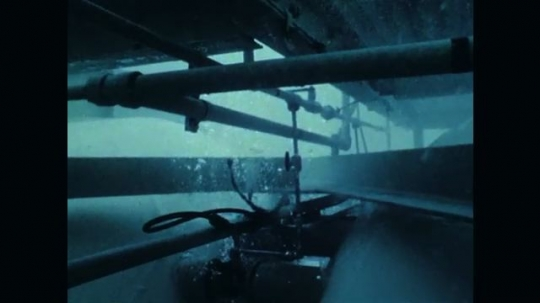 1970s: Underwater views of diving station. Divers swimming.