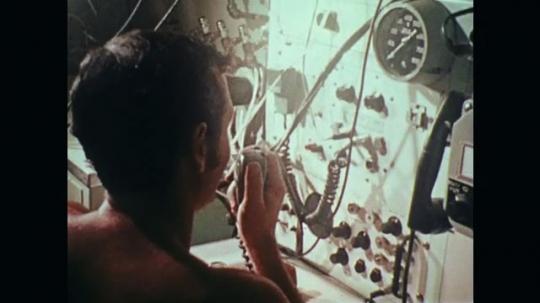 1970s: Man at control panel talks into radio. Diver outside diving station. Man talks into radio. Diver swims through door. Men pulls cords. Underwater view of trap door.
