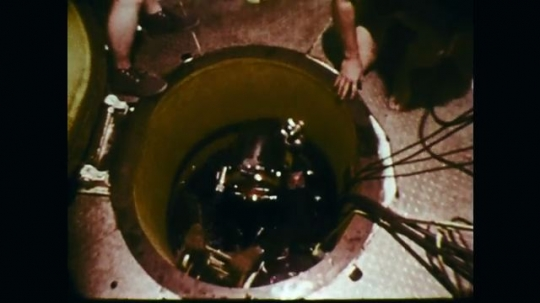 1970s: High angle view, diver climbs through trap door. Men pull cords. Diver swimming with equipment.