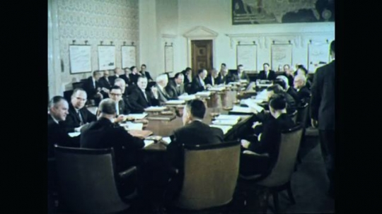 1960s: UNITED STATES: man stands in front of board room attendees. Men sit in meeting. Man picks up wooden hammer