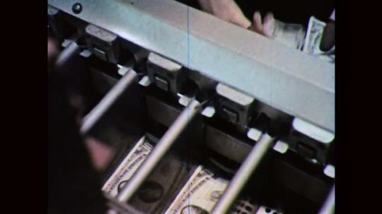 1960s: UNITED STATES: hand sorts money into machine. Dollar bills in machine. Machine stamps dollars.