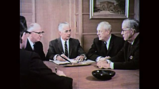 1960s: UNITED STATES: men sit around table in boardroom meeting. Man chairs meeting. Man arrives at work. Husband and wife shake hands with worker